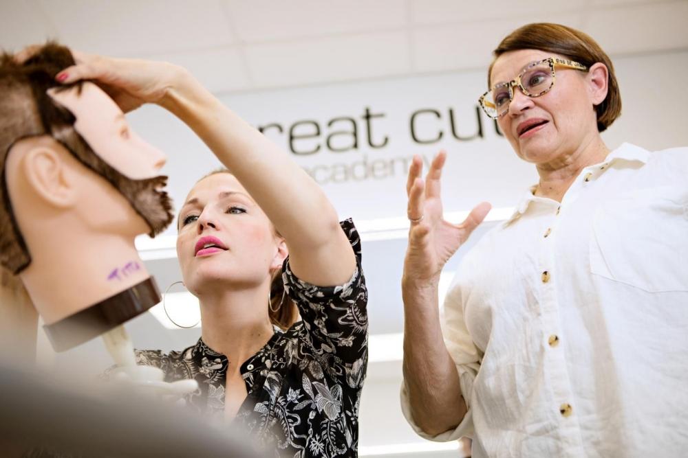 Titta Tervonen (vas.) opiskelee aikuisiällä parturi-kampaajan töihin Tepa Imppolan (oik.) johdolla. Kuva: Eeva Anundi