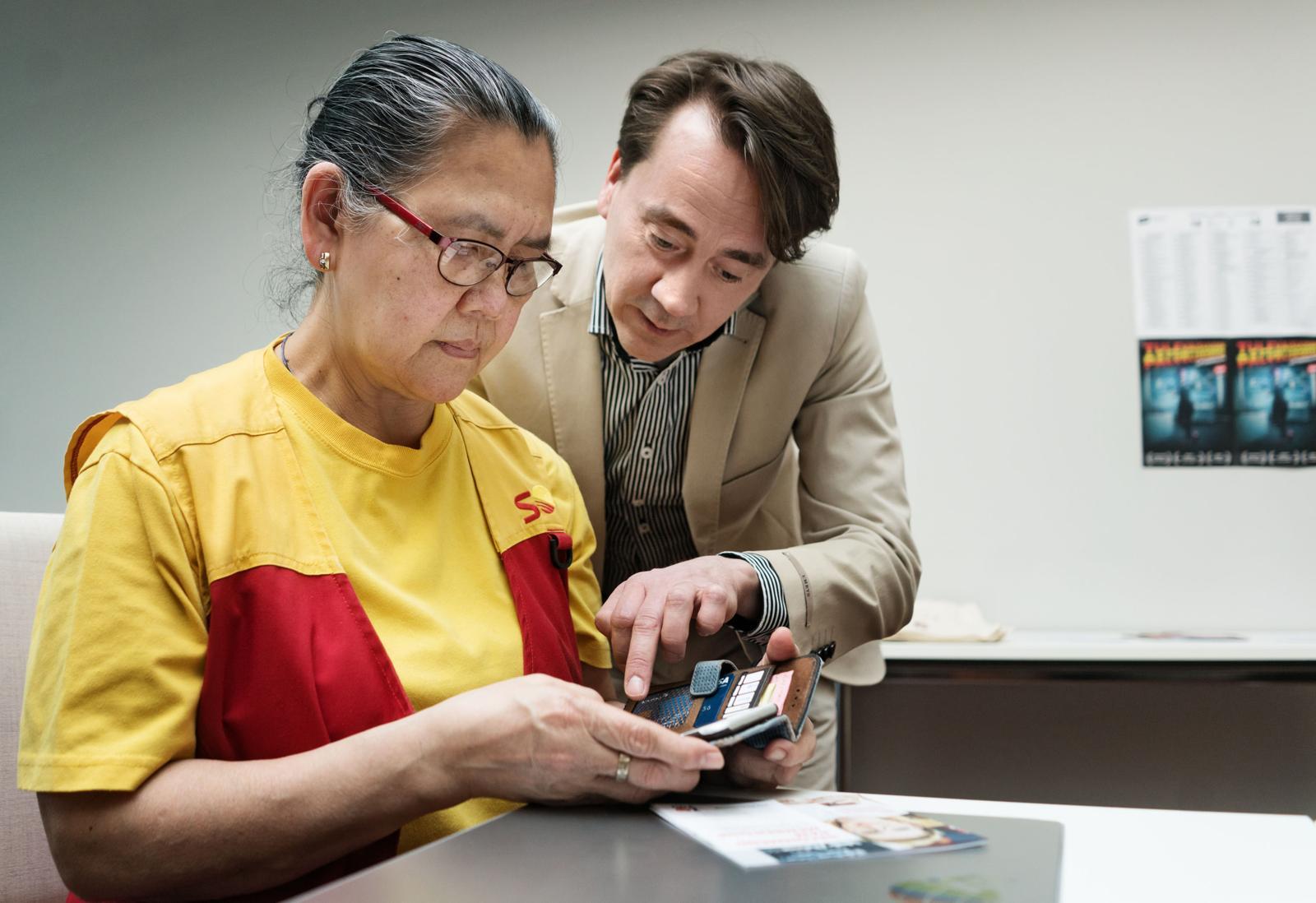 Socorro Cabotaje kysyy, miten kännykällä äänestetään meneillään olevissa liittovaaleissa. PAMin sopimusasiantuntija Raimo Hoikkala kertoo, että tarvitaan vain pankkitunnukset ja ehdokkaan numero. Kuva: Jukka Rapo