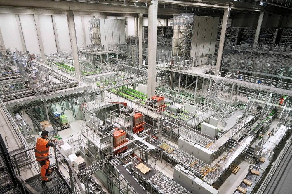 Hannu Ylikotilan eteen aukeaa näkymä kuivatavaraosastoon, jossa lattiapinta-ala on täynnä kuljettimia ja muita laitteita. Kuva: Jukka Rapo