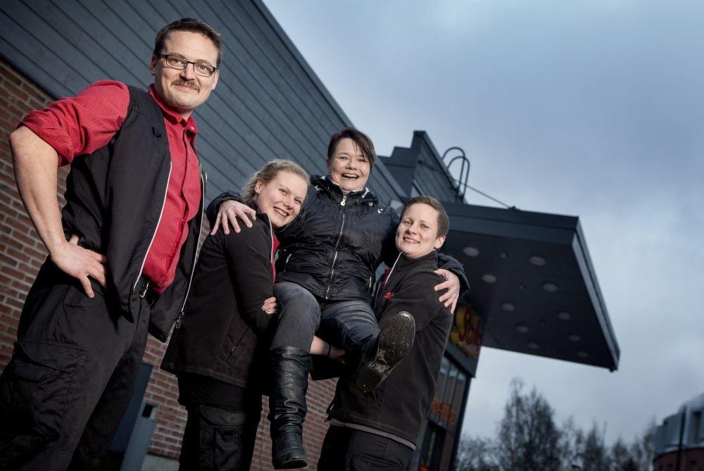 Tiia Jumppanen (oik.) ja Ella Penttilä nostavat asiakkaansa Kati Tuulolan kultatuoliin. Vasemmalla myymäläpäällikkö Anssi Vilen. Kuva: Kati Laukkanen