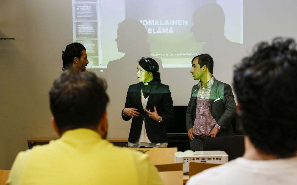 Tulkki Bahaulddin Rawi (vas.), pappi Laura Kajala ja PAMin aktiivi Berhan Ahmadi keskustelevat ennen luennon alkua. Kuva: Pasi Leino
